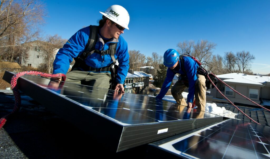 man in blue jacket and white helmet standing on blue and white solar panel during daytime